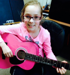 Charlotte with her guitar at JLA Music