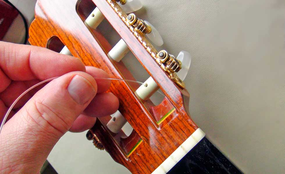 Pass the First String Through the Hole in the Tuning Peg