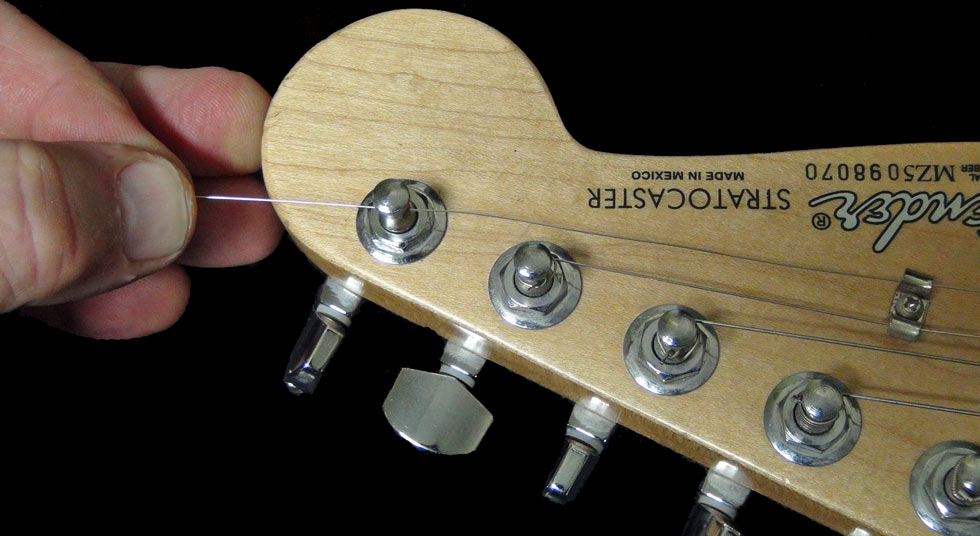 Pass the string through the hole in the tuning peg