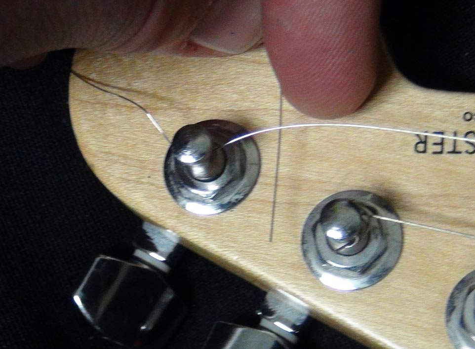 Pass the end of the string under the part of the string on the other side of the tuning peg.